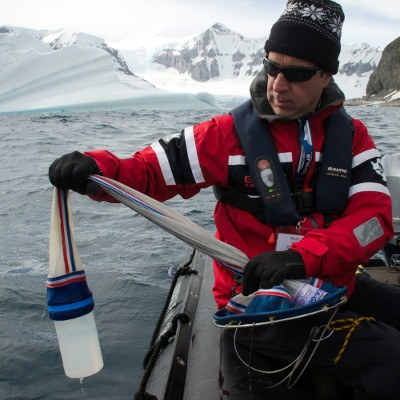 citizen scientist in Antarctica taking water sample