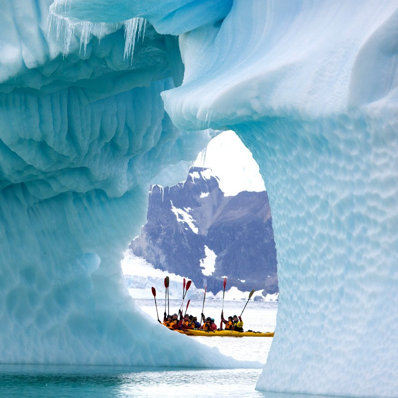 Antarctic kayakers navigating around iceberg